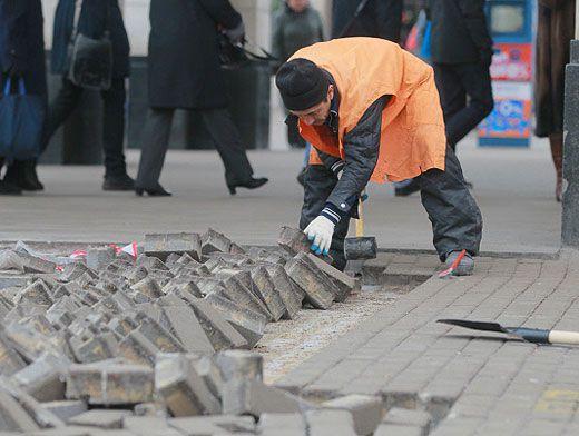 Работа при укладывание брусчатки на дорогах: